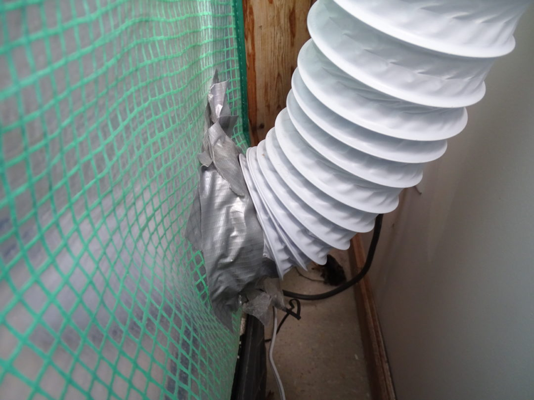 4-inch (10cm) flexible ducting exiting the greenhouse in the lower left-hand corner. The duct tape is there to seal the hole and connect another length of ducting to the fan, which then pushes air and spores outside.
